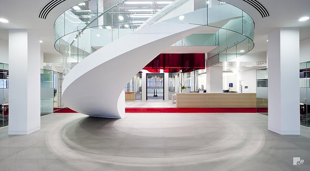 A white winding staircase with glass balustrade on a concrete floor, in front of a wooden reception desk and a red carpet.