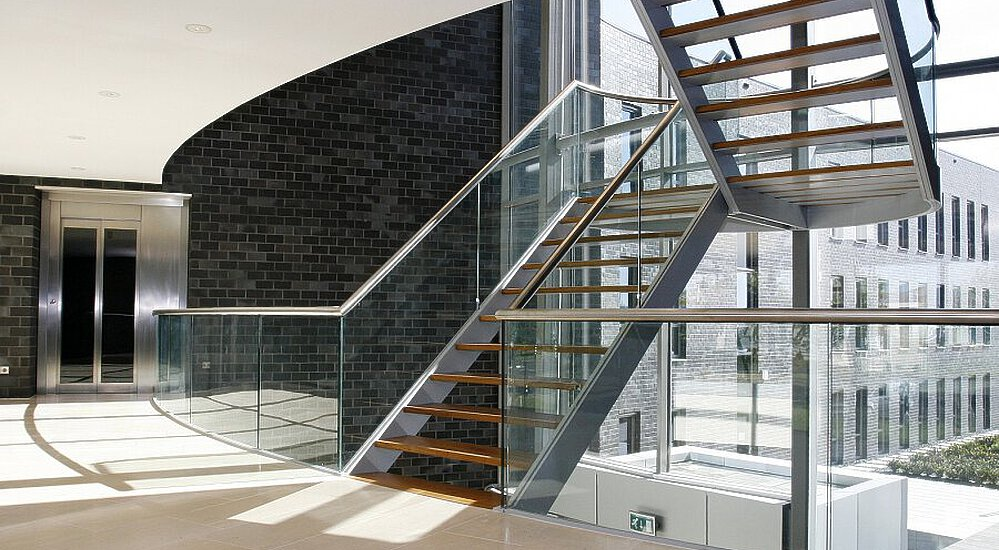 A free-hanging staircase in a hall with a draft lobby with emergency exit sign, a dark brick wall and a glass façade.
