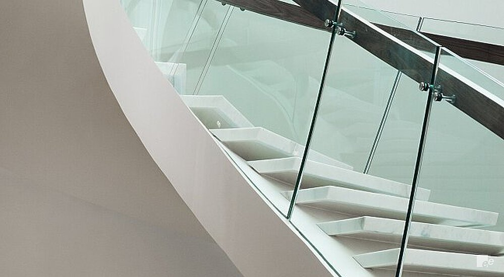 A winding staircase with white natural stone treads and underside and fitted with extra-high glass balustrades.