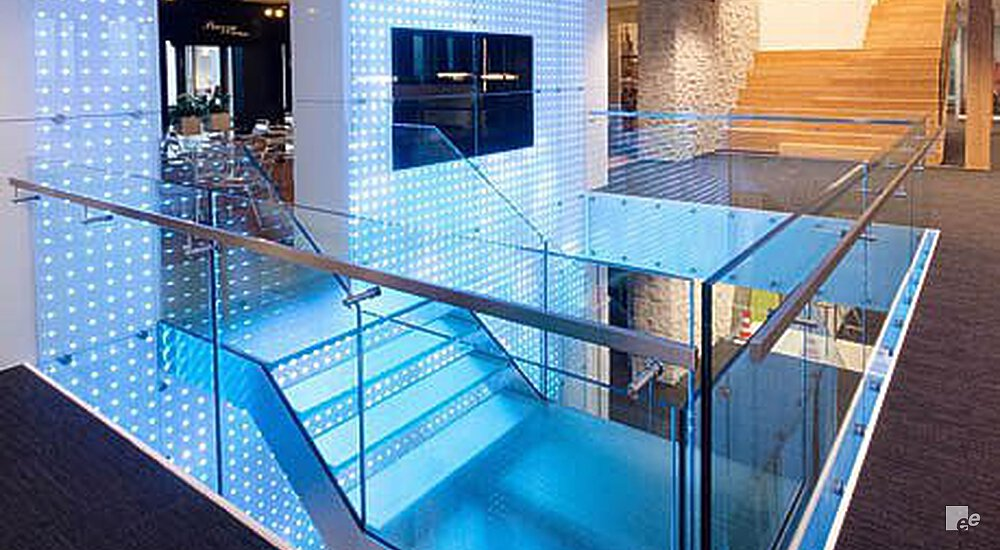 The staircase in the lobby of Vodafone Amsterdam, surrounded by a glass balustrade in blue light.