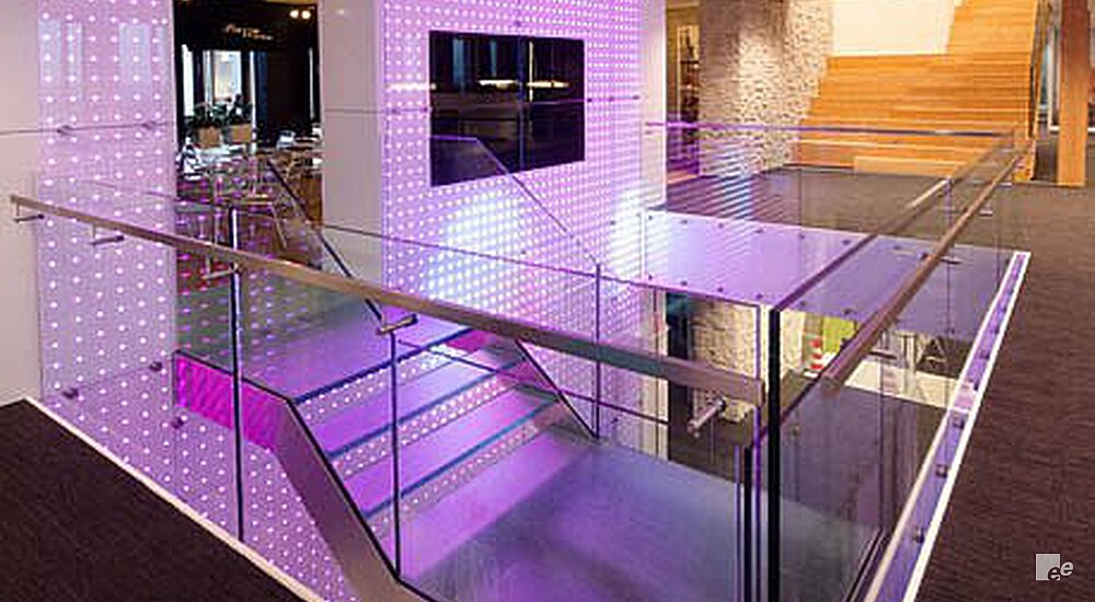 A wall with LED lighting colours the staircase, balustrade and parquet floor in the lobby of Vodafone Amsterdam purple.
