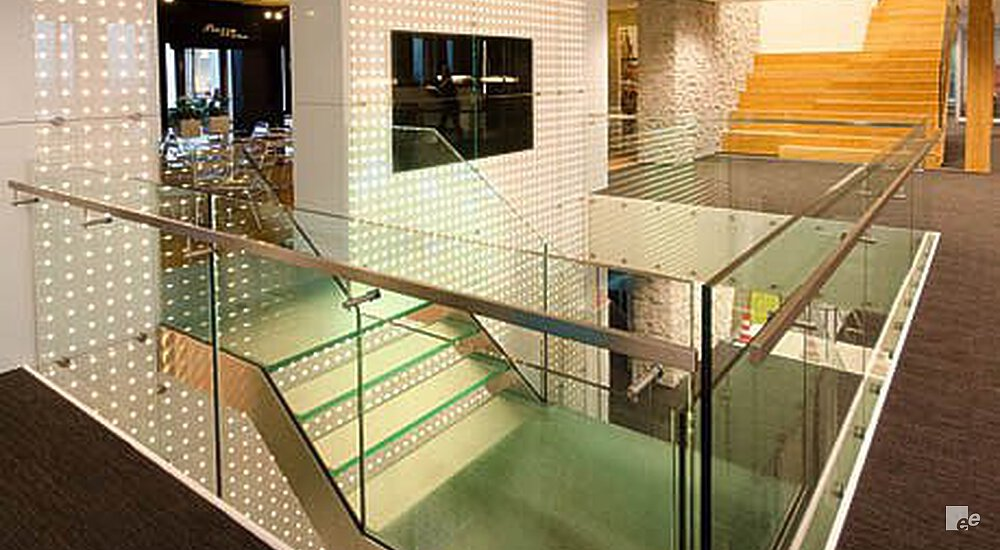 A glass balustrade, parquet floor, staircase and wall with green LED lighting in the lobby of Vodafone Amsterdam.