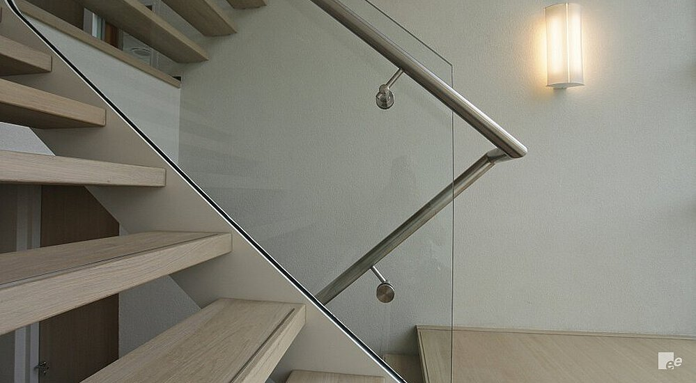 Wooden staircase treads, a glass balustrade and a wooden landing, in front of a white stucco wall and a lamp.