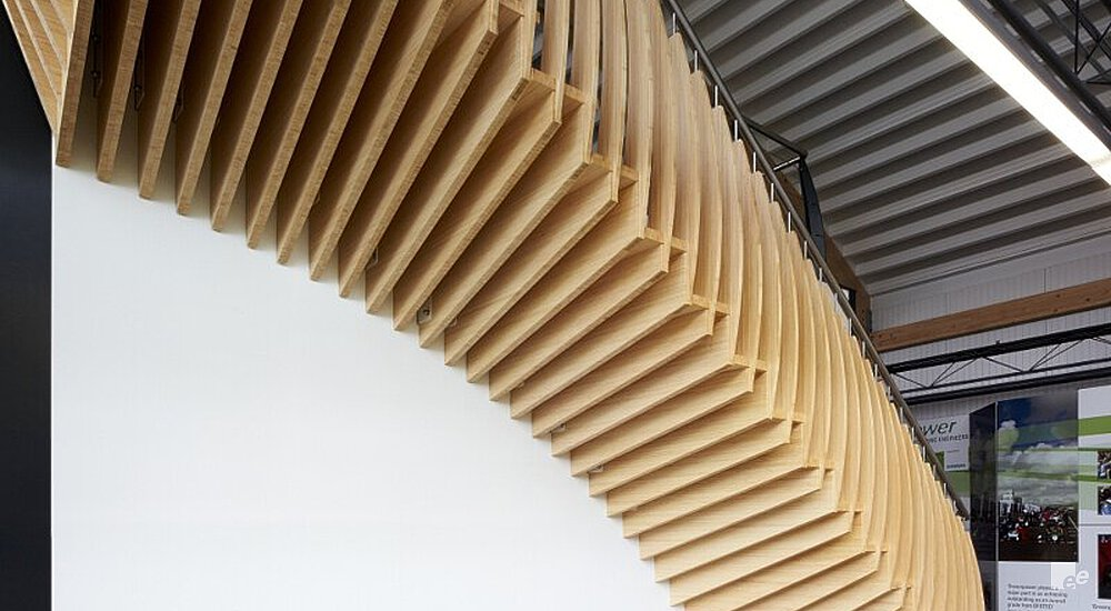 The underside of a bamboo staircase, under a roof with wooden rafters and curved corrugated sheets.