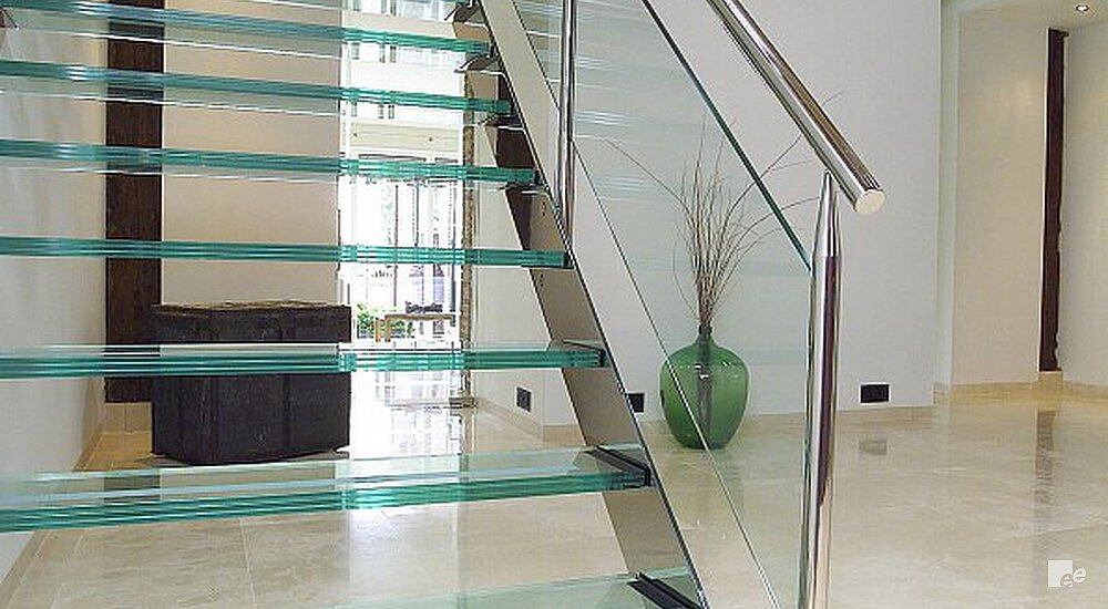 An Open Glass Stairway On A Marble Floor In A Hall With Wooden Beams And A