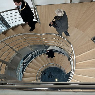 People walking the staircase with bamboo treads in the building of Kanes Foods in Worcestershire.