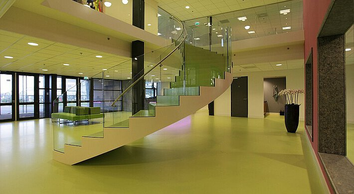 A winding staircase with glass balustrades in an office with a cast floor, pillar, dark flowerpot and ceiling lighting.