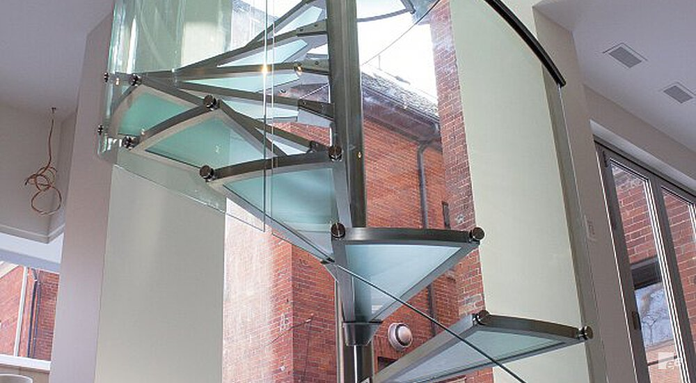 A spiral staircase with glass balustrade, in a stairwell by window frames and a white stucco ceiling.