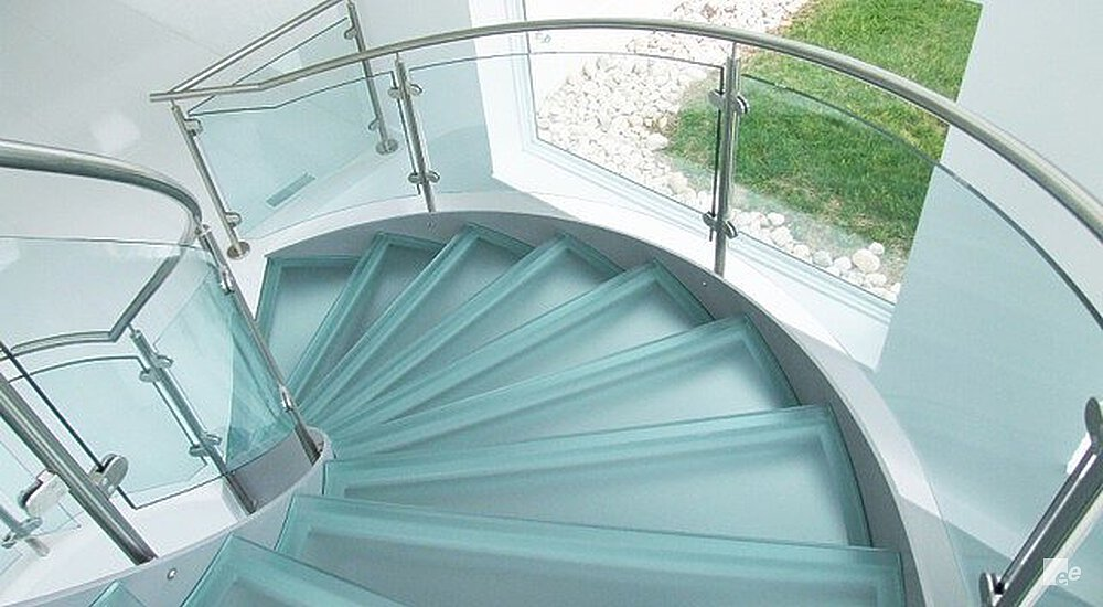 A winding staircase with frosted glass treads and glass balustrades, next to a window frame with a view of grass.