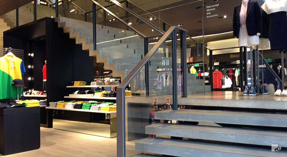 The landing staircase in the Lacoste shop in London has concrete treads, glass balustrades and wooden handrail.