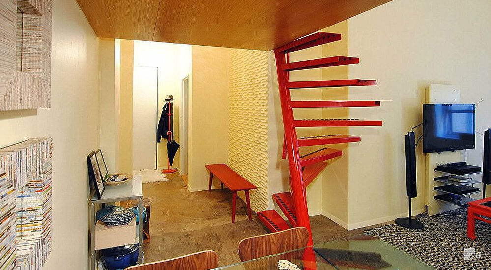 A space-saving staircase below a wooden loft and by a glass table, wooden chairs and audio system.