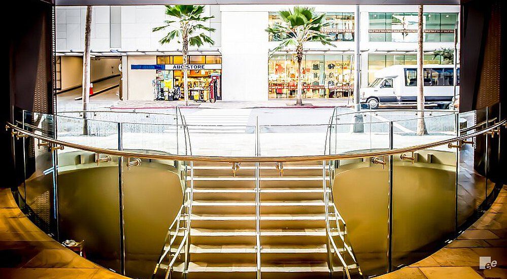 A staircase and balustrade in the Waikiki Shopping Plaza, with a view of palm trees and a van.