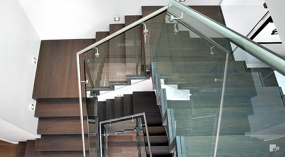 A waterfall staircase with dark oaken treads and a glass balustrade in a residence in Toronto.