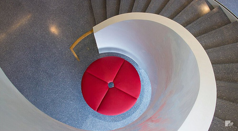 The winding staircase around a table and above a cast floor in the Ontario Institute of Cancer Research.