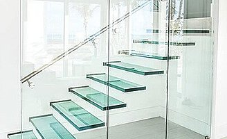 A floating glass staircase with a stainless steel staircase rail, behind a glass wall by a white stucco wall.