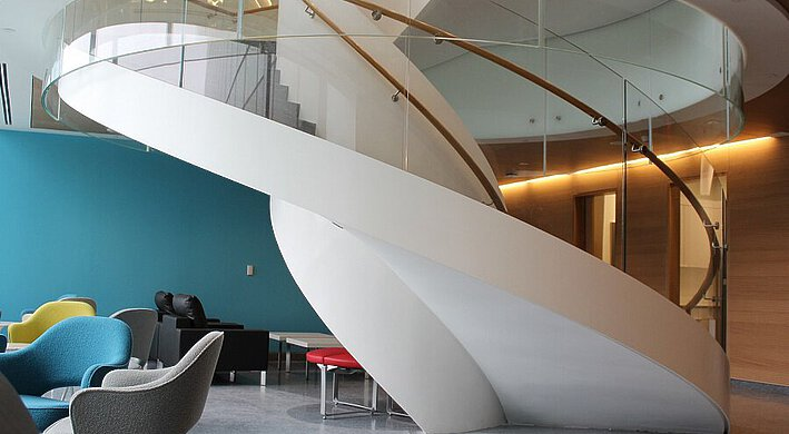 The winding staircase in the offices of OICR in Toronto, with cast floor and ball chairs.