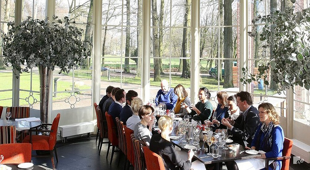 People on chairs at a table in a conservatory with a dark cast floor, ficuses and high windows.