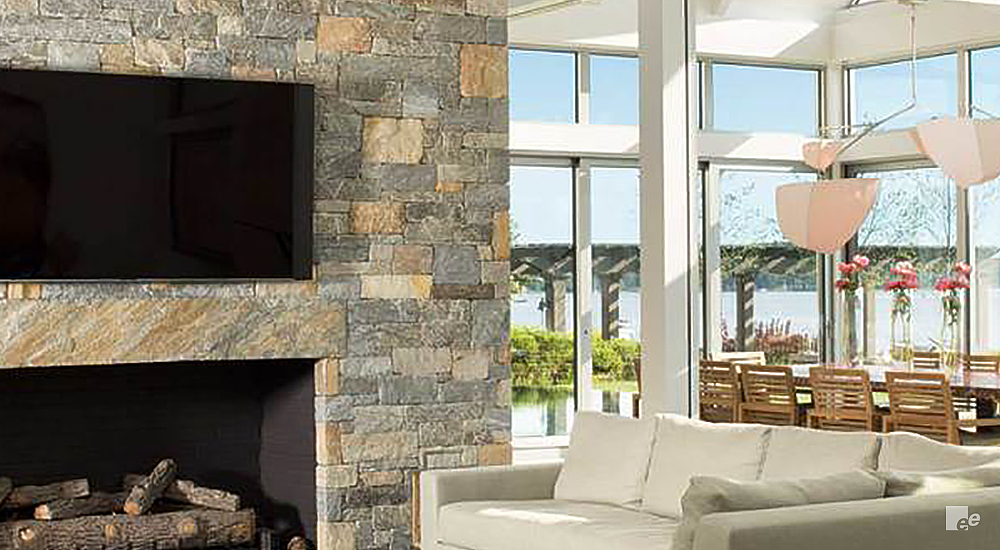 Living room with a TV on a stone wall, a fireplace underneath. White corner sofa with wooden dining table behind it with wooden chairs.