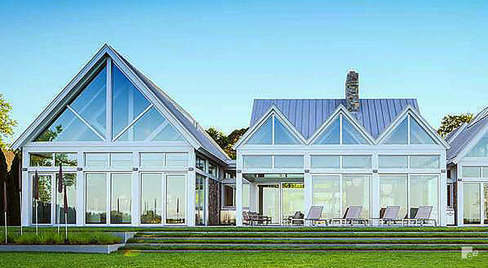 Building with lots of windows and glass facade, stone chimney. Outside are chairs and grass.