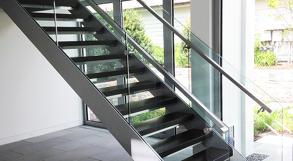 Staircase with stainless steel stringers, stainless steel handrails and glass railings.