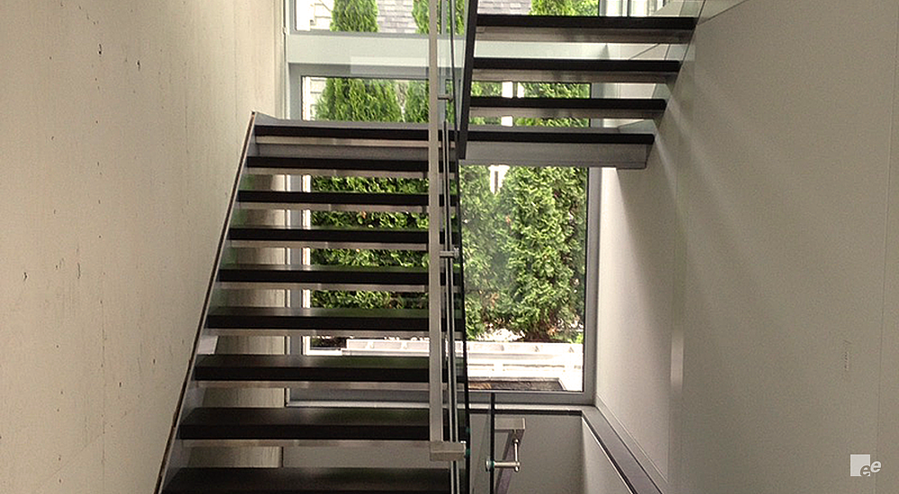 Straight staircase with wooden steps and landing, a window behind it with trees outside.