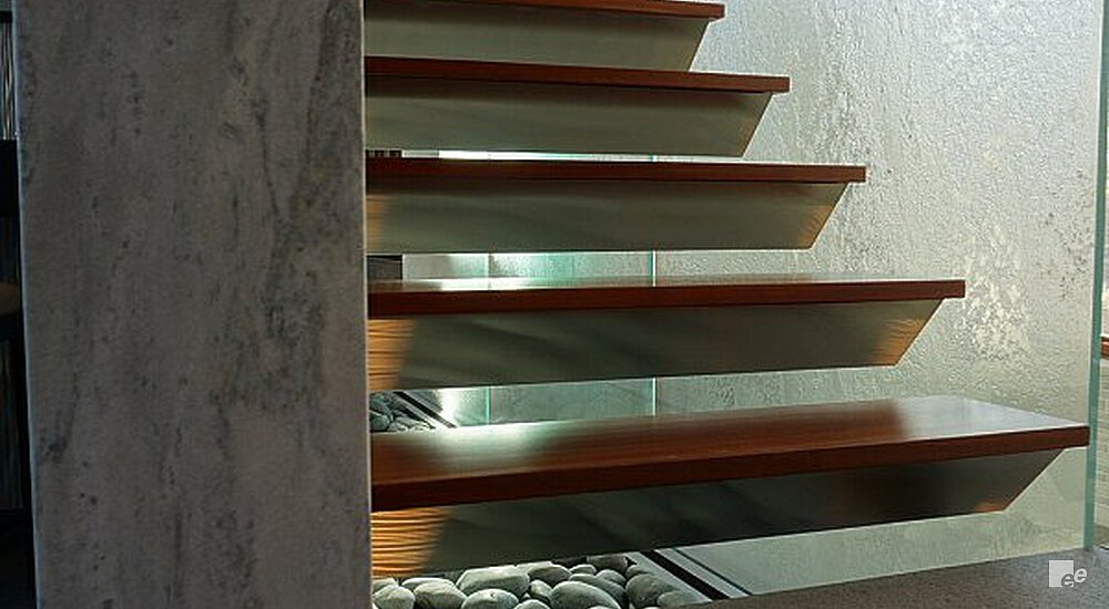 Bottom view of a floating wooden staircase right along a glass wall, cobblestones are underneath the stairs.
