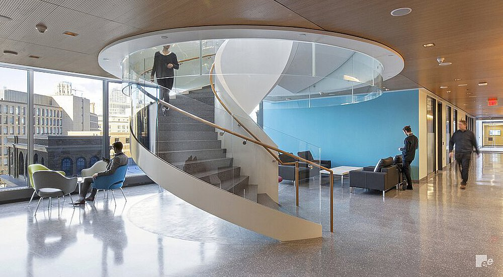 Spiral staircase in the middle of an area with armchairs and sofas, with an acoustic wooden ceiling.