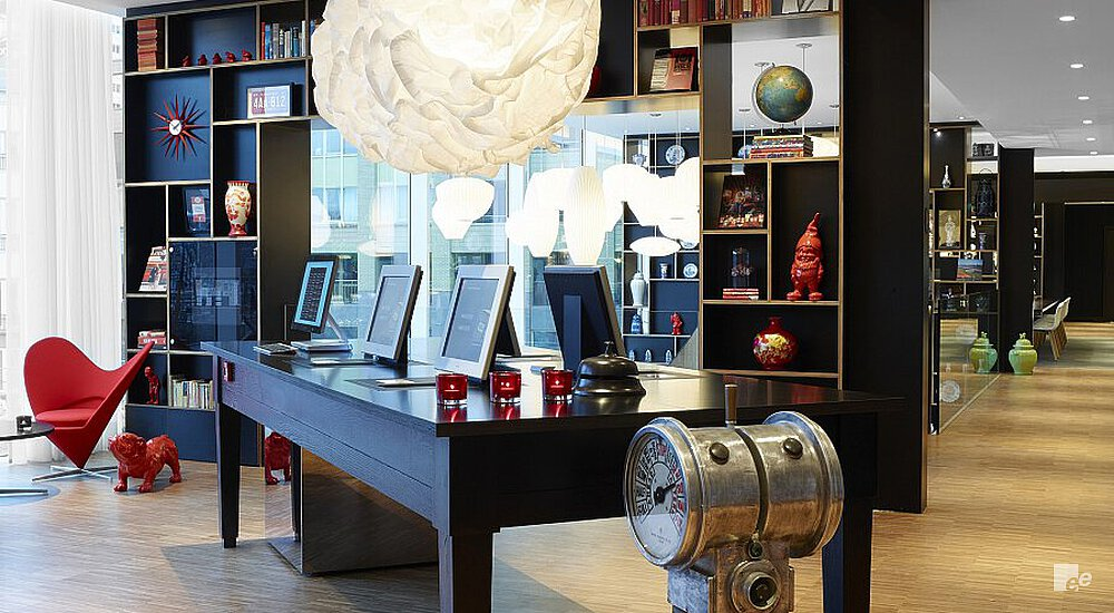 Black table with monitors, a wooden floor, eccentric ceiling light and cabinets with artifacts and books.