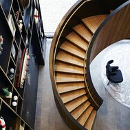 A closed winding staircase on a floor with oblong tiles, carpet, lounge chair and wall cabinet with a model boat inside.