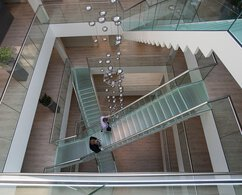 Top view of several glass steps that overlap, with stainless steel handrails and glass railings, that two men are walking on