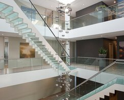 The atrium of LIMES, glass stairs with stainless steel handrails and glass railings, large ceiling light, plant and painting.