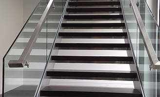 A straight staircase with glass railings and square stainless steel handrails
