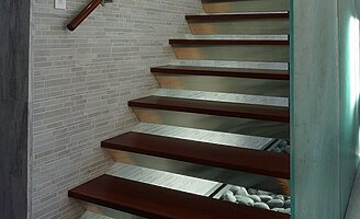 A wooden floating staircase, with a wooden handrail fixed to the wall. Grey cobblestones are underneath the stairs.