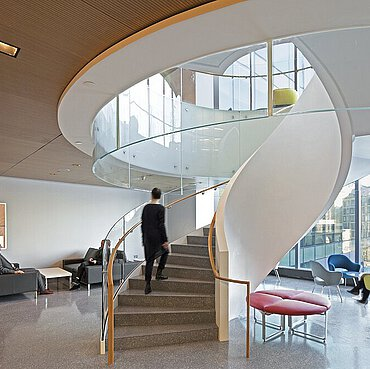 Area with armchairs, wooden ceiling, business environment, spiral staircase with golden handrails and glass balustrade.