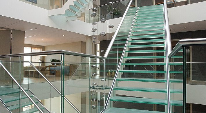 Glass steps on top of each other in an atrium, with a ceiling light, black walls, a painting and plants.