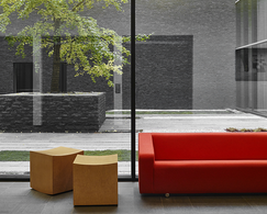 Two large windows with a red sofa and two square chairs inside, and an inner courtyard outside with a tree and a wall.