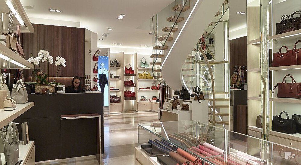 Overview of Longchamp Paris, a bag shop, with a desk, bags and spiral staircase.
