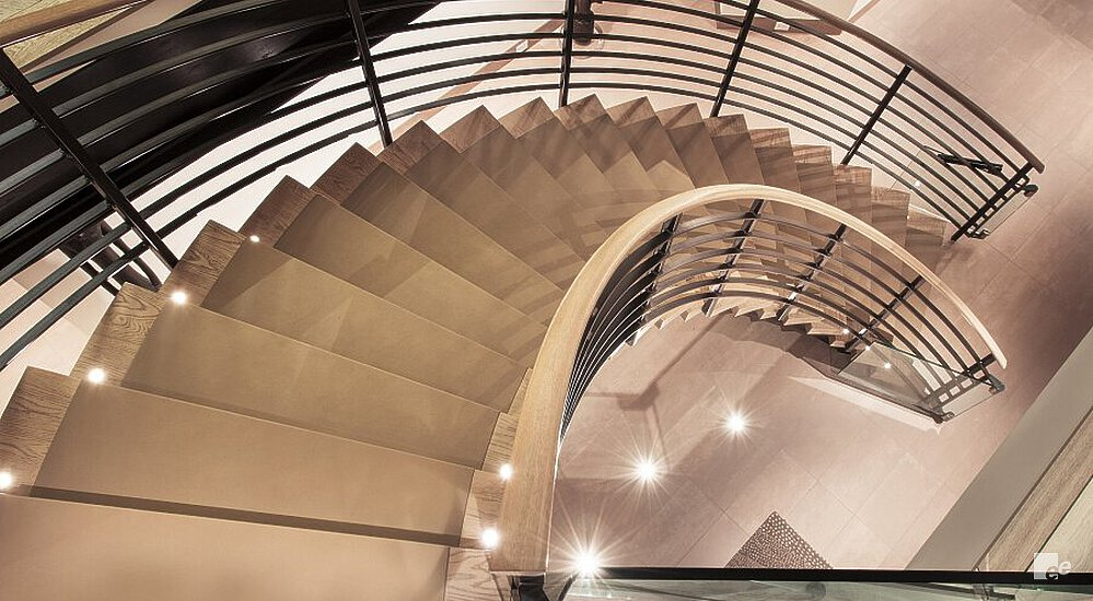 A top view of a spiral staircase with leather-covered wooden steps, and wooden floor.