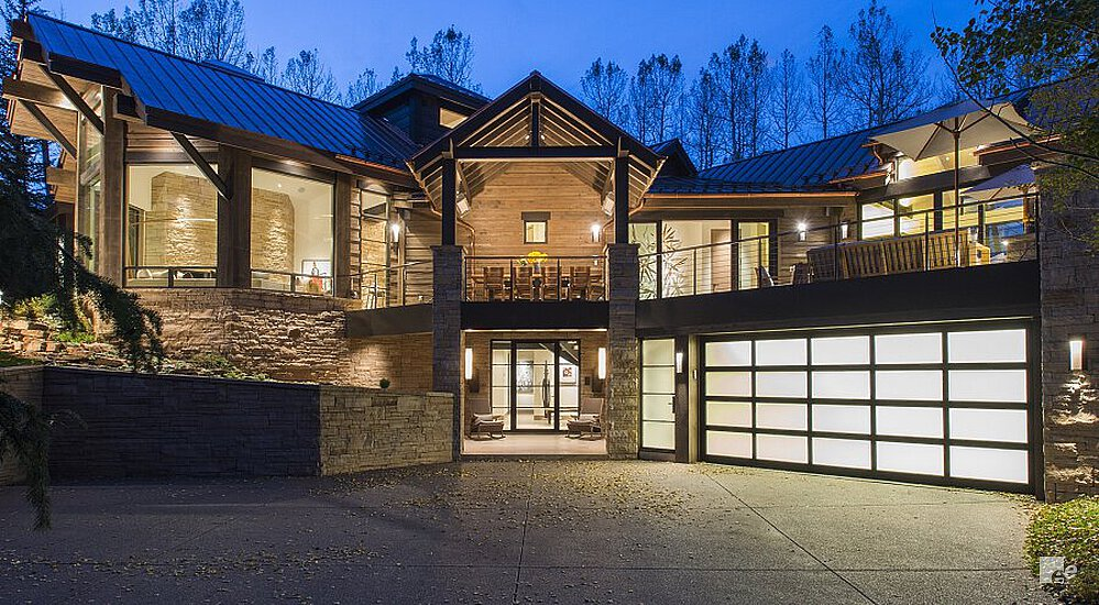 Modern house with a huge glass exterior, the lights are on.