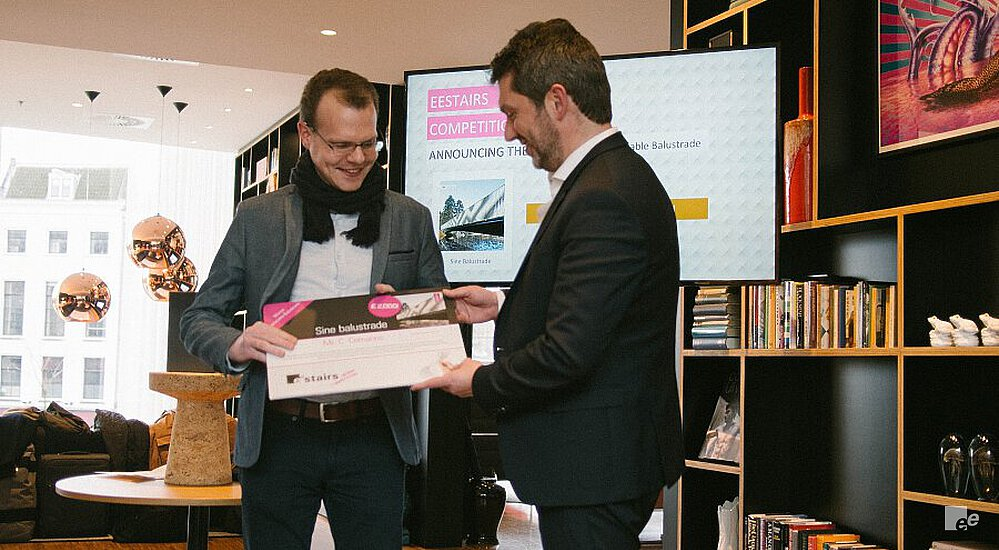 Van Vlastuin is presenting an award in the citzienM hotel in Rotterdam, in front of a case with books and artifacts.