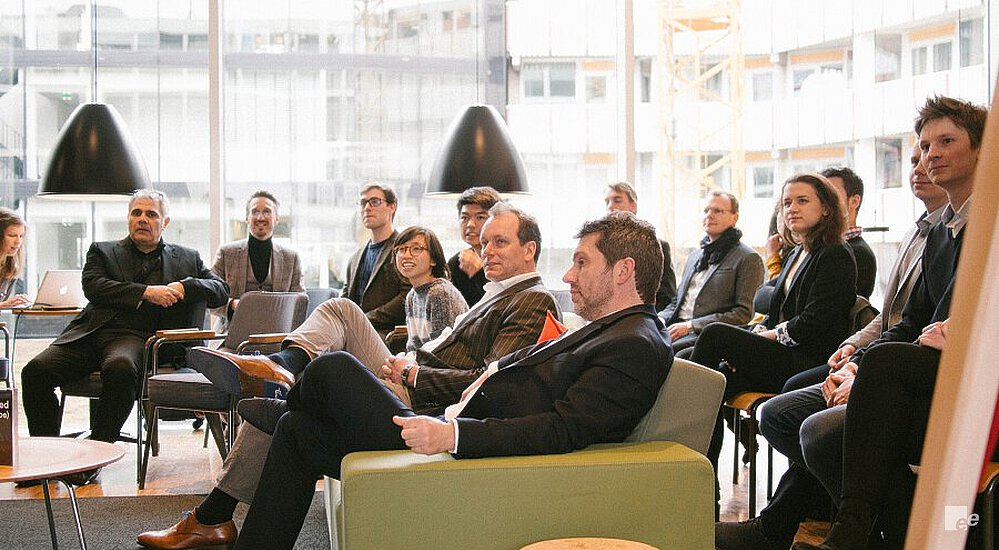 Van Vlastuin and Cluistra on a green sofa with a stool made of cork in front of them, and behind them the participants of the EeStairs Design Competition.