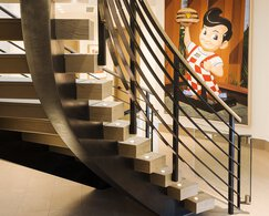 A rear view of a spiral staircase with steel mid-rails and a large painting on the wall.