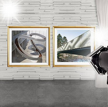 A camera that is taking a picture of two paintings, which depict the winning designs.